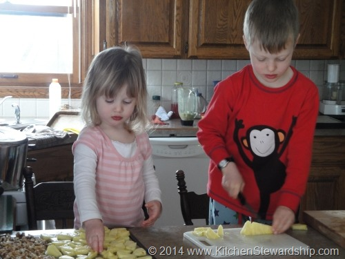 kids in the kitchen - cutting pineapple to dehydrate