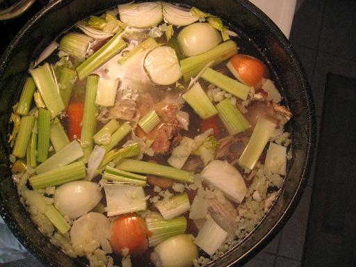 Looking down at a stock pot filled with water, meat, and veggies