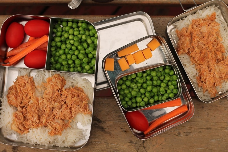 kids bento lunchboxes packed with shredded chicken, peas, cheese, tomatoes and carrots
