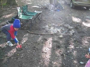 Young boy digging in the dirt.