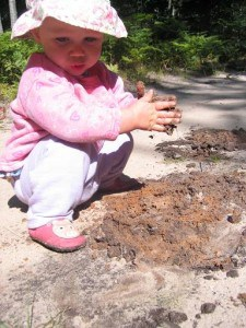 Toddler girl playing in the dirt.