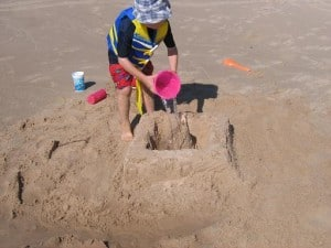 Young boy pouring water into a sand castle