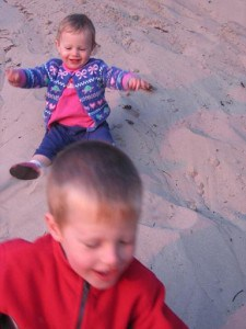 Toddler girl and young boy sliding in the sand.