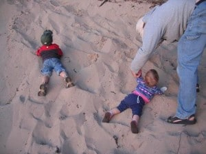 Young boy and toddler girl laying in the sand.