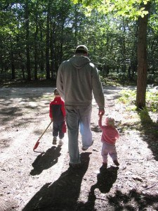Dad, toddler and young boy walking in the woods
