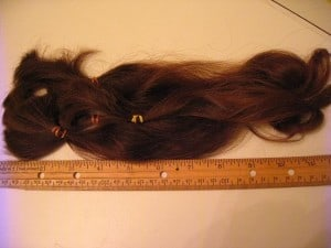 Using a rule to measure hair that has been cut