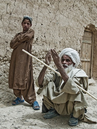 Blind man praying in a crouching position with a young boy looking at him from behind.