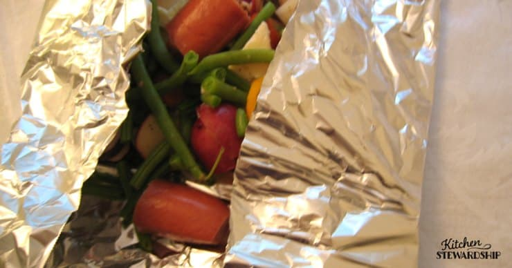Package of veggies and hot dogs in foil, campingfood