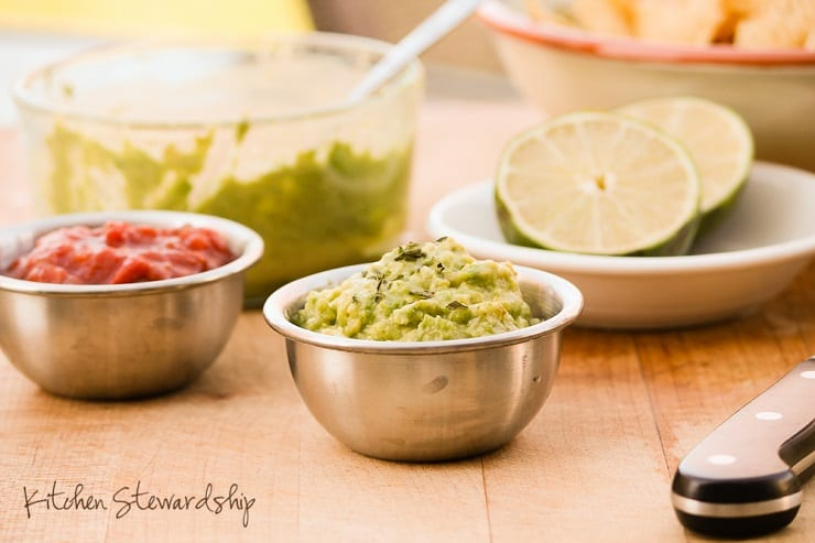 A stainless steel bowl of guacamole on a wooden plank table