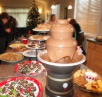 Christmas cookie exchange. Long table with a chocolate fountain and many plates of cookies.