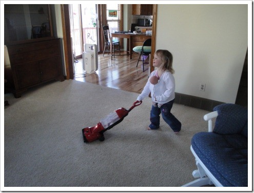 Little girl vacuuming with baby