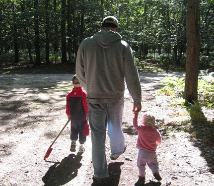 A man walking in the woods with two small children