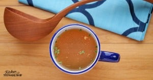 Mug of homemade bone broth with ladle
