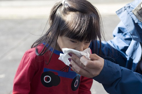 Adult holding a tissue for a child with a cold