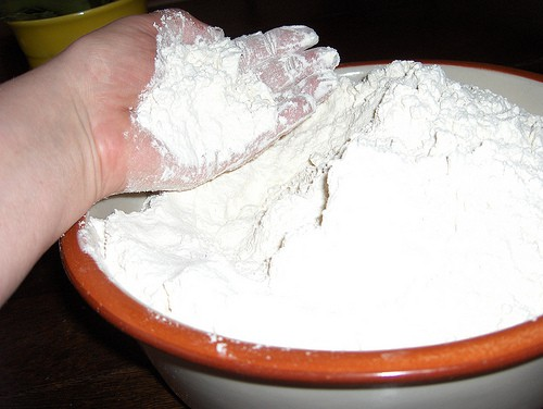Hand scooping flour out of a large bowl