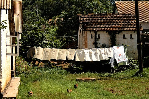 Laundry hanging on a clothesline in front of a rustic farm building