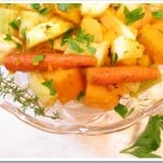 Roasted root vegetables on a glass plate garnished with herbs