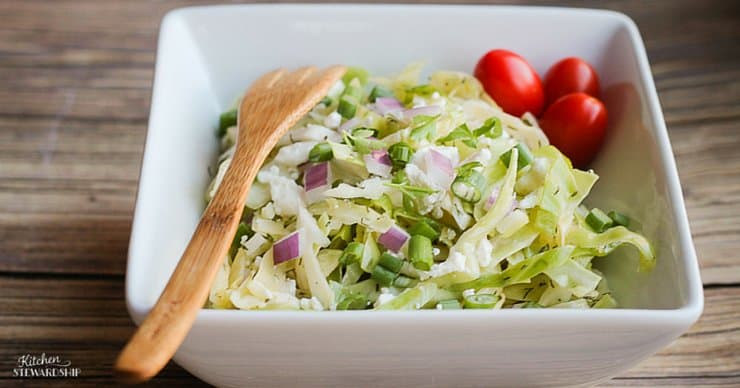 coleslaw in a white bowl with wooden fork