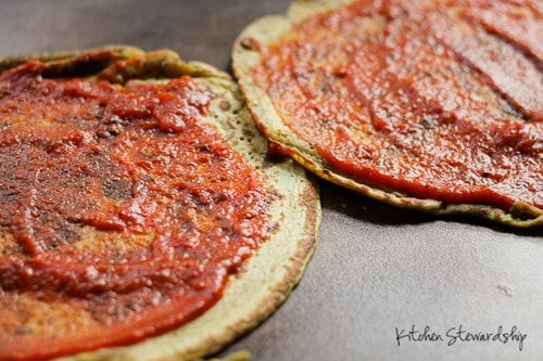 2 cooked chickpea pizza crusts topped with tomato sauce