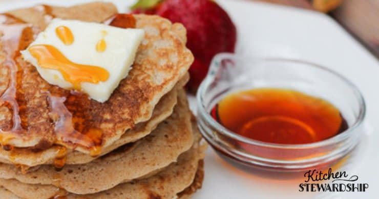 A close-up view of a stack of gluten-free pancakes with a pat of butter and a small bowl of syrup
