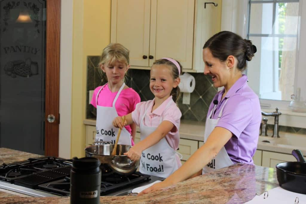child cooking at a stove with parent and friend