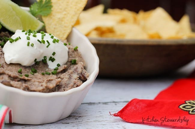 homemade refried beans in a bowl topped with sour cream, lime and chives.