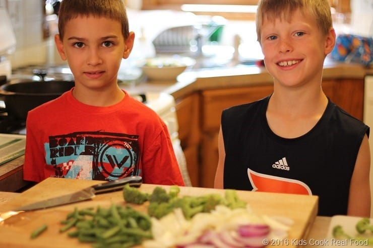 Boys cutting onions and peppers