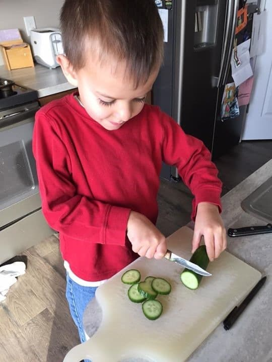 Lesleys son cutting cucumbers