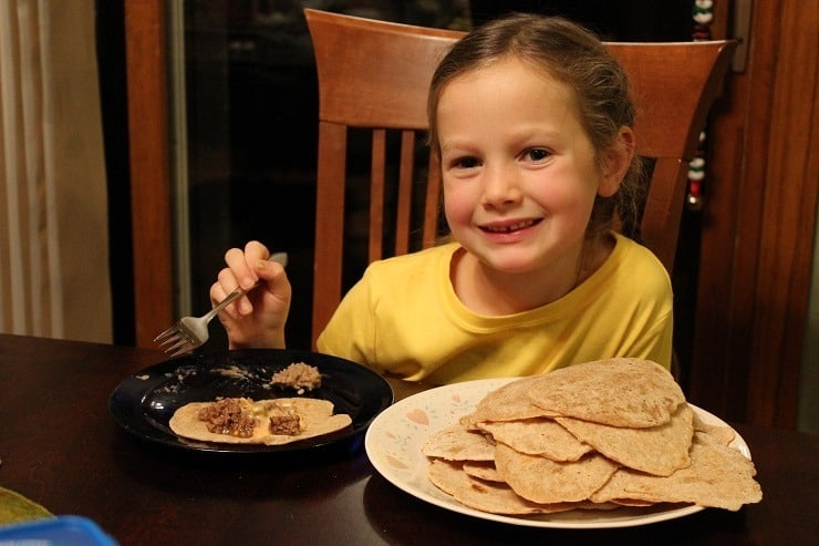 7 year old eating tacos on homemade tortillas she made.