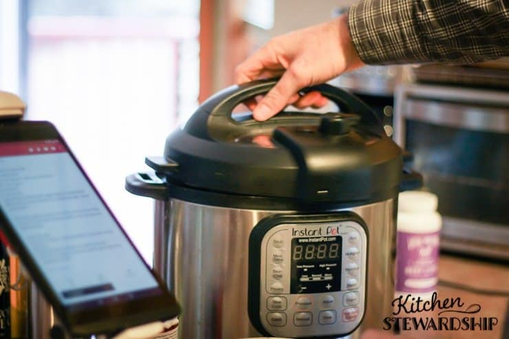 Instant Pot on counter top - man's hand removing lid
