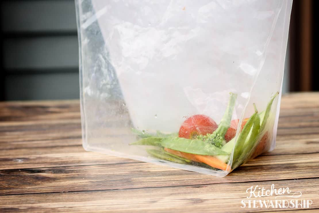 reusable storage bag standing up filled with raw veggies