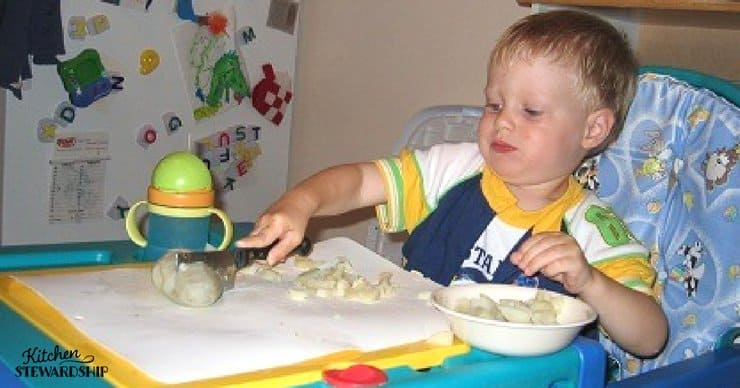 Toddler helping cut boiled potatoes