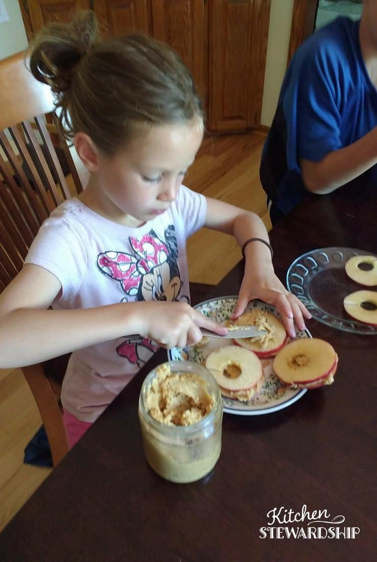 Young girl making nut butter apple sandwiches