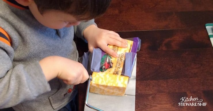 Preschooler learning to slice cheese