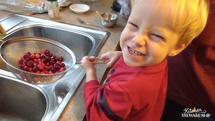 Preschool boy cleaning fresh cranberries.