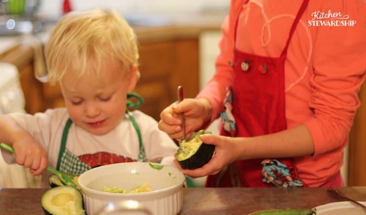 Preschooler learning to make guacamole.