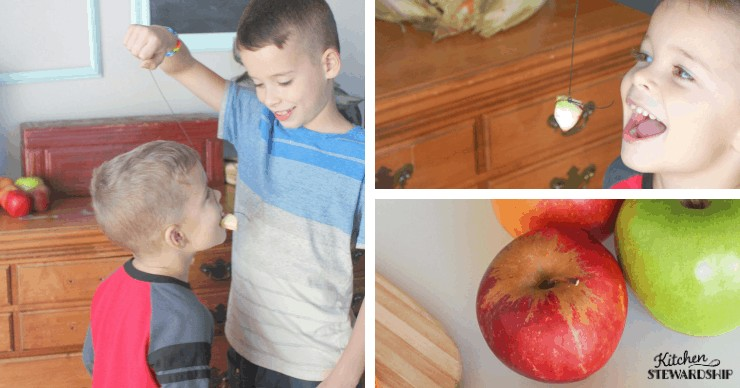 Kids playing a simple fall party game - apples on a string!
