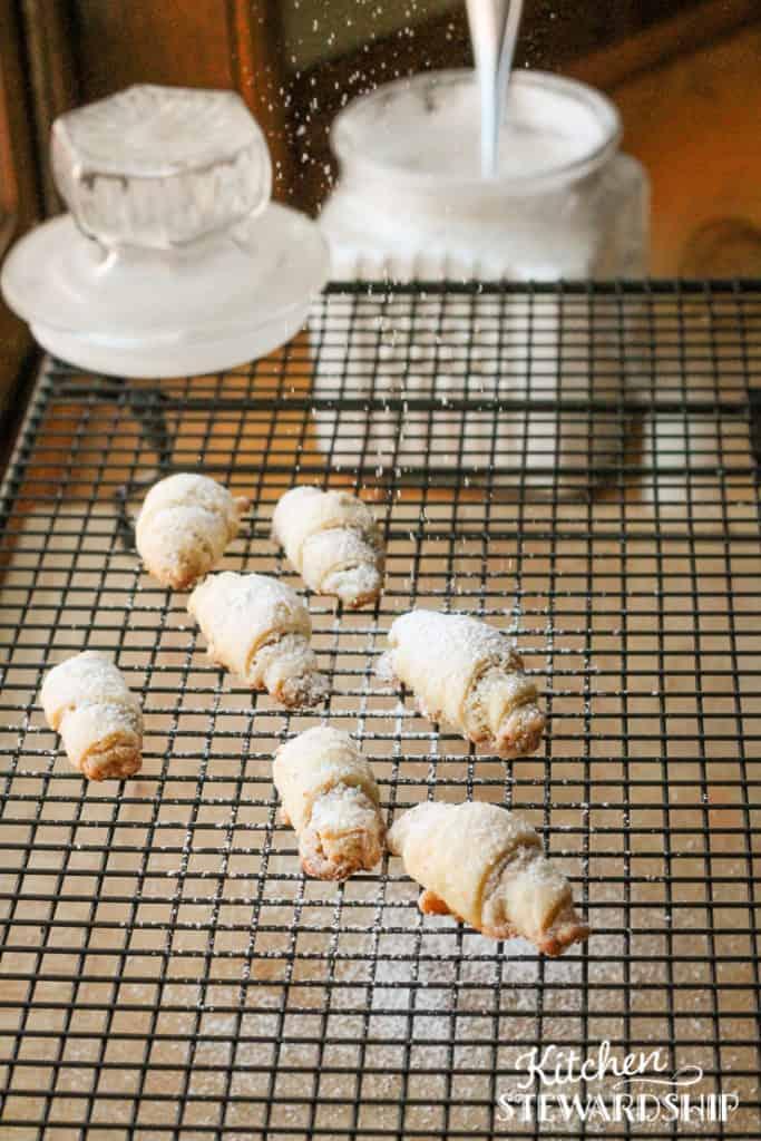 sprinkling powdered sugar on kifli Christmas cookies