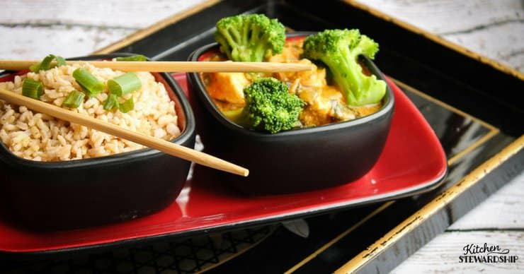 Chopsticks on a bowl of brown rice next to a bowl of chicken curry masala with bok choy and broccoli.