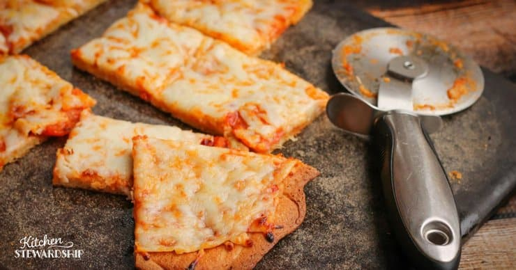 Cheese gluten-free pizza on a pizza stone.