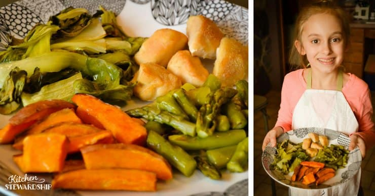 Young girl holding plate with chicken, roasted asparagus, roasted sweet potatoes and bok choy.