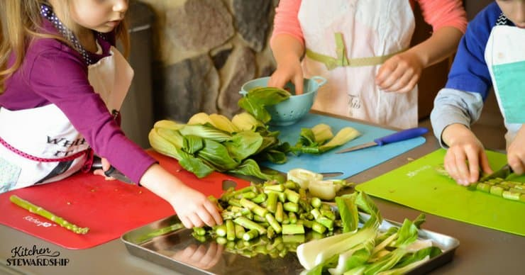 Young kids chopping asparagus and bok choy for an easy sheet pan dinner.