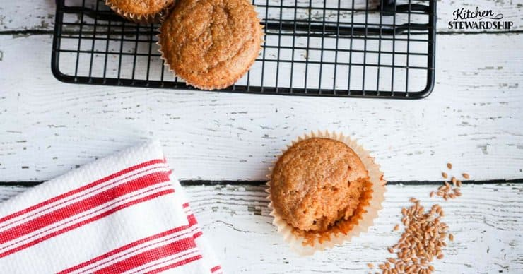 Freshly baked homemade Einkorn applesauce muffins on a table and cooling rack.