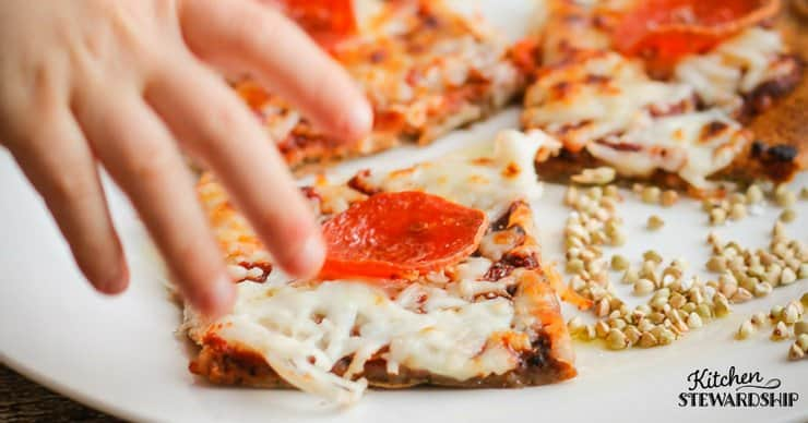Grabbing a piece of freshly baked einkorn pizza with a crispy crust.
