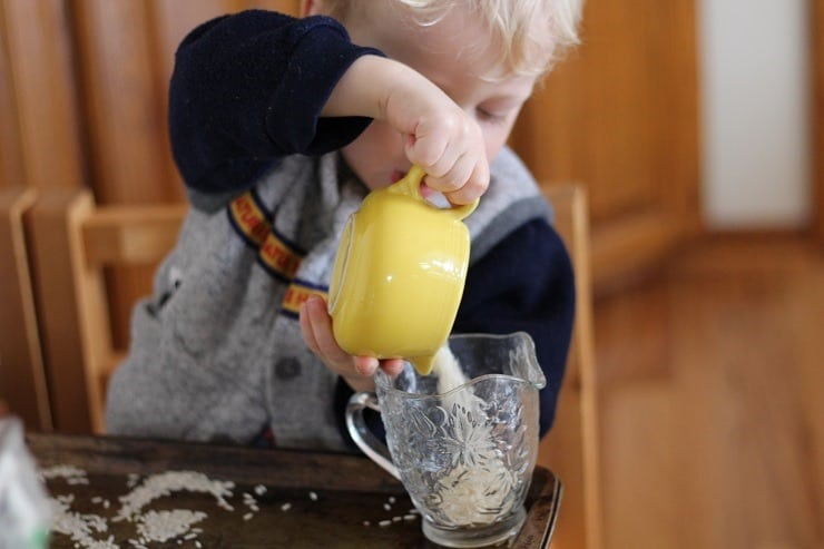 preschool boy pouring rice to learn small motor skills