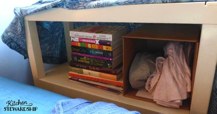Using shelves for a bedside table and covering with fabric to keep things looking tidy.