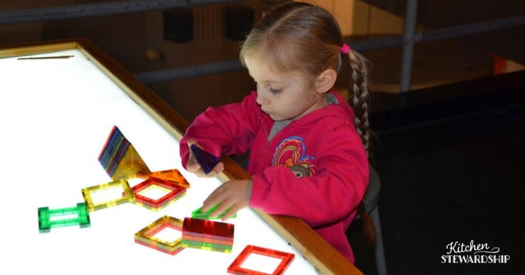 Little girl playing with magna tiles on a light table.