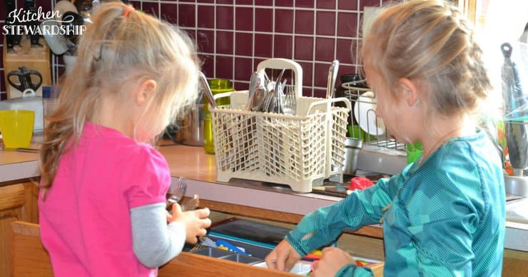 Two young girls putting silverware away.