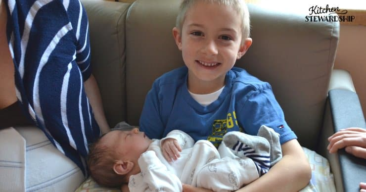 Big brother holding his new baby brother.