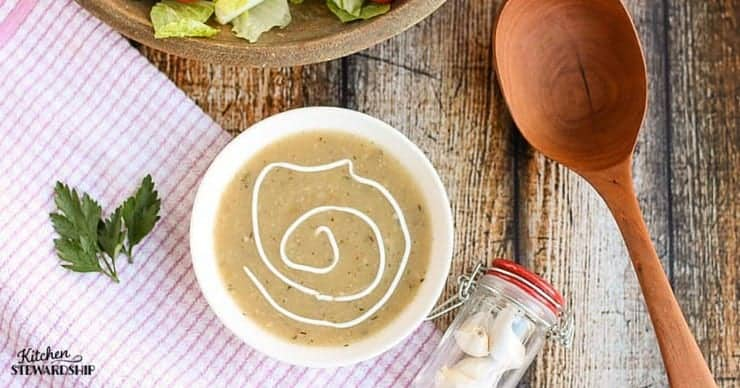 Bowl of garlic soup on a table with salad, wooden spoon and jar of garlic bulbs